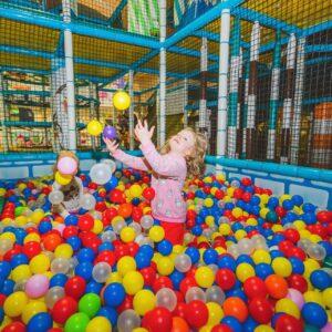 Kaksi lasta leikkii pallomeressä rollohallissa
